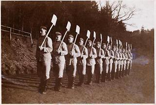 Männer in Uniform mit geschulterten Schaufeln