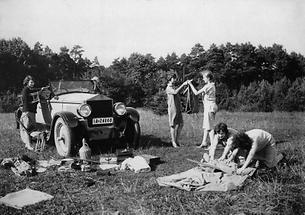 Camping: fünf junge Frauen beim Zeltbau