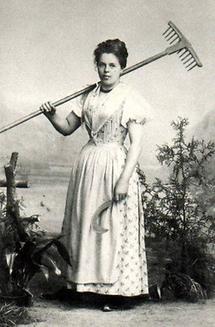 Portrait einer Frau im Dirndl mit Sichel und Rechen