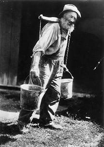 Ein alter Mann beim Wasser tragen