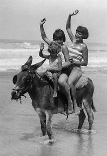 Eine Frau und zwei Kinder reiten auf einem Esel