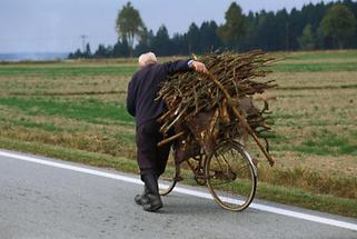 Alter Mann transportiert Holz auf dem Fahrrad