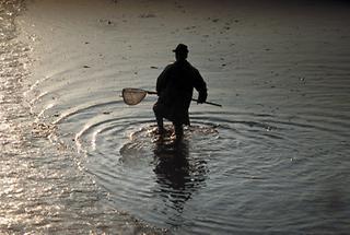 Silhouette eines Fischers mit Fischernetz