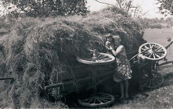 Bäuerin mit Kind vor einem umgestürzten Heuwagen