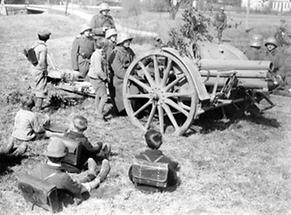 Interessierte Schulkinder beobachten eine militärische Übung