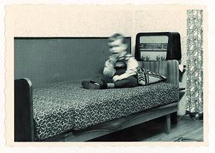 Junge von ca. 4 Jahren sitzt auf einem Sofa