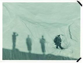 Ein Skiwanderer mit Rucksack liegt in einer Schneemulde