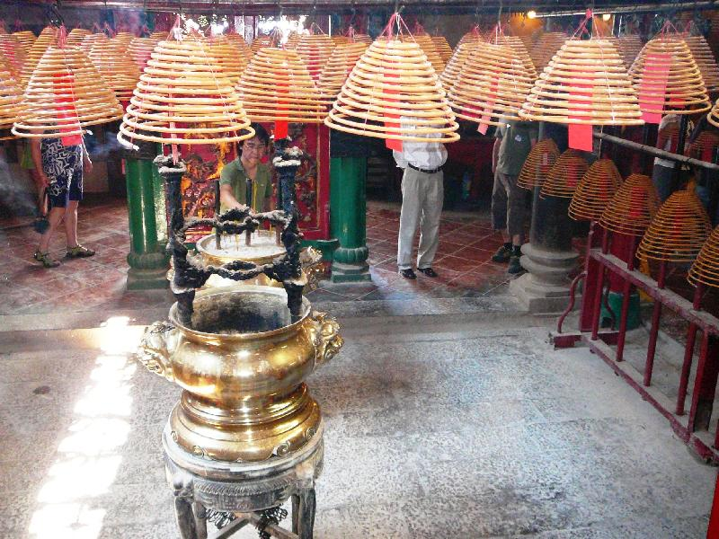 Devotees burn sacrifice money and huge bell-shaped coils of incense that hang from the temple
