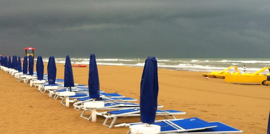 Sandy Beach with umbrellas and sunbeds