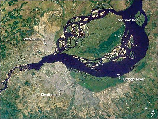 This astronaut image shows two capital cities (brownish-gray areas) on opposite banks of the Congo River. The smaller city on the north side of the river is Brazzaville, while the larger, Kinshasa, is on the south side. The cities lie at the downstream end of an almost circular widening in the river known as Stanley Pool. The international boundary follows the south shore of the pool (roughly 30 km in diameter). The Republic of the Congo, originally a French colony, is sometimes called Congo-Brazzaville - as opposed to the Democratic Republic of the Congo (known from 1971 to 1999 as Zaire) which is often called Congo-Kinshasa, originally a Belgian colony. Brazzavilles population is less than a tenth of Kinshasas. There is no bridge between the cities so that water craft of many kinds ply between them. It is not uncommon to see dugout canoes being paddled between the cities. Photo courtesy of NASA.