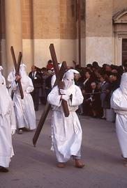 Hooded repenters pull or carry crosses.