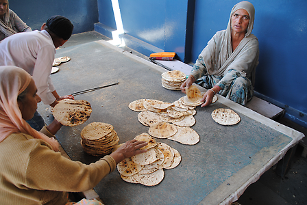 Women lay flatbread on top of each other for distribution