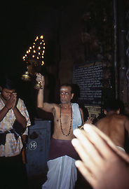 A temple servant blesses the pilgrims with a large chandelier